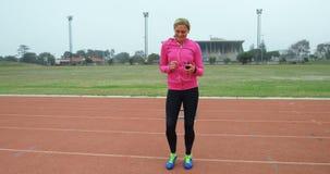 Música que escucha del atleta de sexo femenino en el teléfono móvil mientras que ejercita en circuito de carreras metrajes