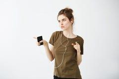 Música que escucha del baile alegre loco de la chica joven en auriculares sobre el fondo blanco Foto de archivo libre de regalías