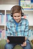 Música que escucha del colegial feliz mientras que usa la tableta digital en biblioteca Imagen de archivo