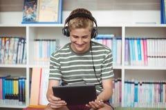 Música que escucha del colegial feliz mientras que usa la tableta digital en biblioteca Imagen de archivo libre de regalías