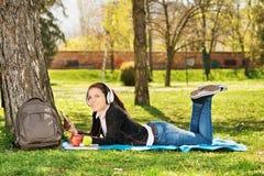 Música que escucha del estudiante hermoso en el parque Foto de archivo