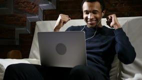 Música que escucha del hombre africano en el ordenador portátil y baile en la noche