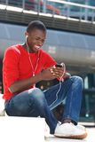 Música que escucha del hombre africano joven en el teléfono celular Foto de archivo