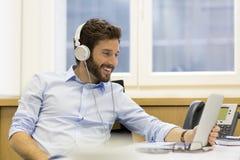 Música que escucha del hombre alegre y ordenador con en oficina moderna Imagen de archivo