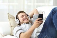 Música que escucha del hombre feliz en casa Imagen de archivo