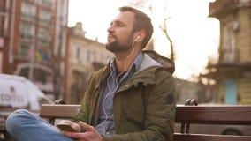 Música que escucha del hombre hermoso en auriculares en el parque de la ciudad que se sienta en banco almacen de video