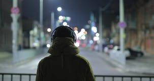 Música que escucha del hombre irreconocible en auriculares en la ciudad de la noche almacen de metraje de vídeo