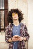 Música que escucha del hombre joven con el teléfono móvil Imágenes de archivo libres de regalías