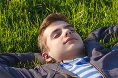 Música que escucha del hombre joven del teléfono elegante en la hierba en el parque Imágenes de archivo libres de regalías
