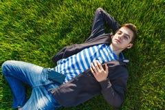 Música que escucha del hombre joven del teléfono elegante en la hierba en el parque Imagen de archivo