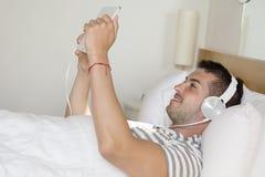 Música que escucha del hombre joven en la cama Imagen de archivo