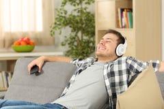 Música que escucha del hombre relajado en casa Fotografía de archivo libre de regalías
