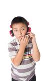 Música que escucha del muchacho asiático con los auriculares, aislados en el CCB blanco Imágenes de archivo libres de regalías