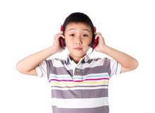 Música que escucha del muchacho asiático con los auriculares, aislados en el fondo blanco Fotografía de archivo