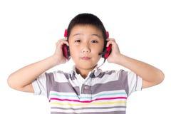 Música que escucha del muchacho asiático con los auriculares, aislados en el fondo blanco Foto de archivo libre de regalías