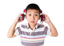 Música que escucha del muchacho asiático con los auriculares, aislados en el fondo blanco Imagen de archivo