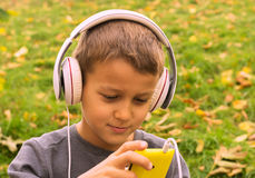 Música que escucha del muchacho con los auriculares Fotografía de archivo