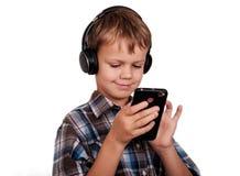 Música que escucha del muchacho europeo con el teléfono móvil aislante Imagen de archivo libre de regalías