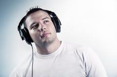 Música que escucha del muchacho joven en auriculares Fotografía de archivo