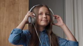 Música que escucha del niño feliz o muchacha sonriente linda con los auriculares de los sonidos