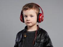 Música que escucha del niño pequeño en auriculares Niño divertido Fotografía de archivo libre de regalías