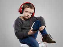 Música que escucha del niño pequeño en auriculares Niño divertido Imagen de archivo