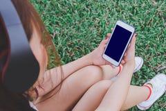 Música que escucha del teléfono elegante con los auriculares Imágenes de archivo libres de regalías