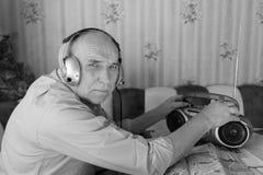 Música que escucha del viejo hombre de la radio en monocromo Imagenes de archivo