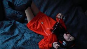 Música que escucha en los auriculares que mienten en cama, visión superior de la muchacha almacen de video