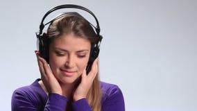 Música que escucha encantadora de la mujer joven en auriculares metrajes