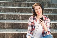 Música que escucha femenina hermosa alegre de un smartphone Foto de archivo libre de regalías