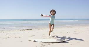 Música que escucha femenina y baile en la playa