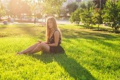 Música que escucha hermosa de la mujer joven en el parque Fotografía de archivo