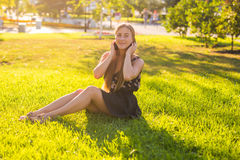 Música que escucha hermosa de la mujer joven en el parque Imagenes de archivo