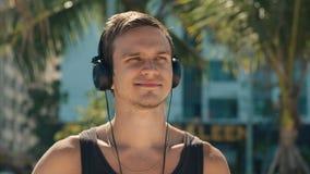 Música que escucha hermosa del hombre joven de su Smartphone en los auriculares blancos inalámbricos, bailando en la playa urbana almacen de video