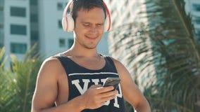 Música que escucha hermosa del hombre joven de su Smartphone en los auriculares blancos inalámbricos, bailando en la playa urbana almacen de metraje de vídeo