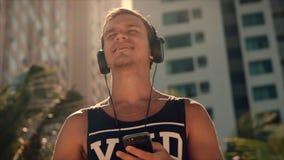 Música que escucha hermosa del hombre joven de su Smartphone en los auriculares blancos inalámbricos, bailando en la playa urbana metrajes
