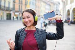 Música que escucha mp3 del estudiante feliz al aire libre y que muestra el cellph Fotos de archivo