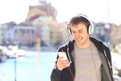 Música que escucha que camina del adolescente del teléfono elegante Fotos de archivo libres de regalías