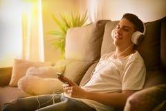 Música que escucha relajada del adolescente en sitio con la atmósfera caliente Imagen de archivo