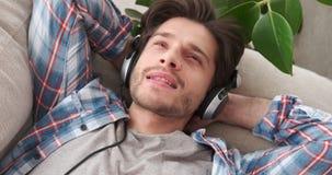 Música que escucha relajada del hombre joven en los auriculares almacen de metraje de vídeo