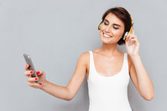 Música que escucha sonriente de la chica joven en smartphone con los auriculares Fotografía de archivo libre de regalías