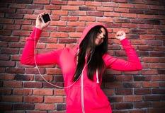 Música que escucha sonriente de la chica joven y baile en auriculares Imagenes de archivo