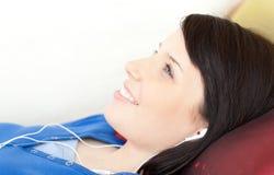 Música que escucha sonriente de la muchacha adolescente que miente en un sofá Imagen de archivo