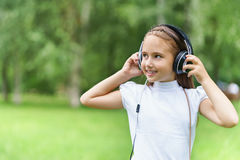 Música que escucha sonriente de la muchacha caucásica de los jóvenes con los auriculares profesionales de DJ y la diversión el co Imagenes de archivo