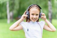 Música que escucha sonriente de la muchacha caucásica de los jóvenes con los auriculares profesionales de DJ y la diversión el co Foto de archivo
