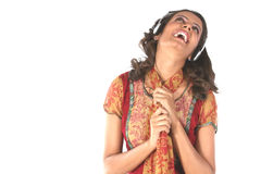 Música que escucha sonriente de la muchacha con los teléfonos principales Foto de archivo libre de regalías