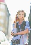 Música que escucha sonriente de la muchacha del inconformista en la calle de la ciudad Imagenes de archivo