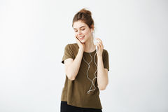 Música que escucha sonriente de la muchacha morena linda joven en hedphones sobre el fondo blanco Imagen de archivo