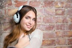 Música que escucha sonriente de la mujer en auriculares Imagenes de archivo